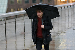© Licensed to London News Pictures. 01/12/2018. London, UK.  A man walking with an umbrella during rain and wet weather, near London Bridge on the first day of meteorological winter.  Photo credit: Vickie Flores/LNP