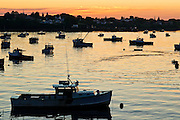 Lobster boats are silhouetted in the bay at sunrise.