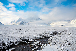 Snow covered winter landscape of Buachaille Etive Mor and River Coupall in Glen Coe in Scottish Highlands, Scotland, UK