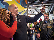 27 NOVEMBER 2019 - DES MOINES, IOWA: US Senator CORY BOOKER (D-NJ) records a Snapchat video with a volunteer after lunch at Central Iowa Shelter and Services in Des Moines. They had to bump elbows rather than shake hands because Sen Booker was wearing gloves to handle food. Sen Booker helped plate up and serve lunch at the shelter. The shelter has about 180 beds and is full almost every night. In January and February, more than 250 people per night come to the shelter, which sets out overflow bedding. Senator Booker is running to be the Democratic nominee for the US Presidency in 2020. Iowa hosts the first selection event of the presidential election season. The Iowa caucuses are February 3, 2020.         PHOTO BY JACK KURTZ