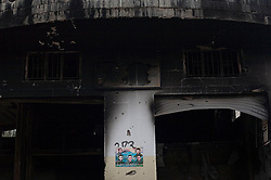 A poster hangs on a damaged building celebrating the five Hezbollah fighters who were killed in the war with Israel in Aytaroun, Southern Lebanon, Oct. 24, 2006.