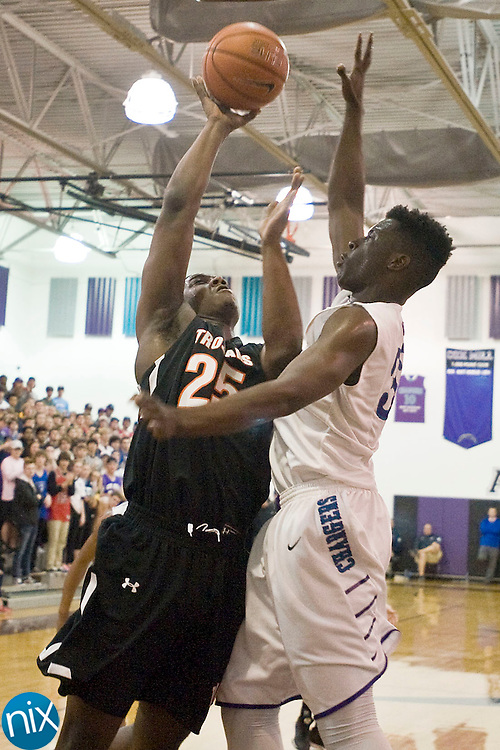 Cox Mill's Jessie Malit (33, right) blocks this shot by Northwest's Anthony Caldwell (25) during the Northwest Cabarrus at Cox Mill 2nd round 3A high school playoff game on Feb. 25.  Cox Mill won with a score of 62 to 54 .
