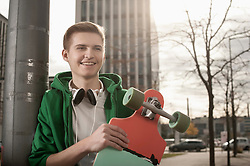 Teenager holding skateboard standing by pole and waiting for someone in street, Bavaria, Germany