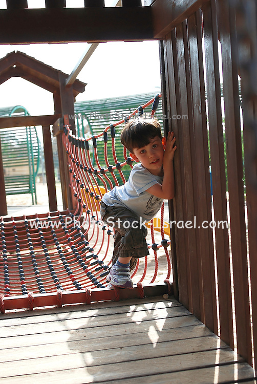 Young boy plays on a jungle Gym