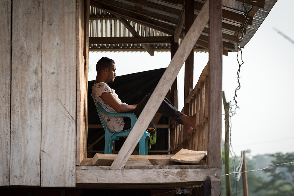 16 November 2018, San José de León, Mutatá, Antioquia, Colombia: As the sun is soon to set, a man sits to rest on the balcony of his house in San José de León. Following the 2016 peace treaty between FARC and the Colombian government, a group of ex-combatant families have purchased and now cultivate 36 hectares of land in the territory of San José de León, municipality of Mutatá in Antioquia, Colombia. A group of 27 families first purchased the lot of land in San José de León, moving in from nearby Córdoba to settle alongside the 50-or-so families of farmers already living in the area. Today, 50 ex-combatant families live in the emerging community, which hosts a small restaurant, various committees for community organization and development, and which cultivates the land through agriculture, poultry and fish farming. Though the community has come a long way, many challenges remain on the way towards peace and reconciliation. The two-year-old community, which does not yet have a name of its own, is located in the territory of San José de León in Urabá, northwest Colombia, a strategically important corridor for trade into Central America, with resulting drug trafficking and arms trade still keeping armed groups active in the area. Many ex-combatants face trauma and insecurity, and a lack of fulfilment by the Colombian government in transition of land ownership to FARC members makes the situation delicate. Through the project De la Guerra a la Paz ('From War to Peace'), the Evangelical Lutheran Church of Colombia accompanies three communities in the Antioquia region, offering support both to ex-combatants and to the communities they now live alongside, as they reintegrate into society. Supporting a total of more than 300 families, the project seeks to alleviate the risk of re-victimization, or relapse into violent conflict.