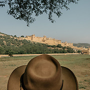 A tourist wearing a hat looks at the Amber Fort. Constructed of red sandstone and marble, the attractive, opulent palace is laid out on four levels, each with a courtyard.