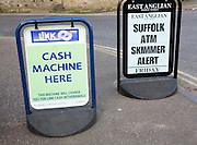 ATM sign outside shop with newspaper headline warning of scam taking place, Suffolk, England