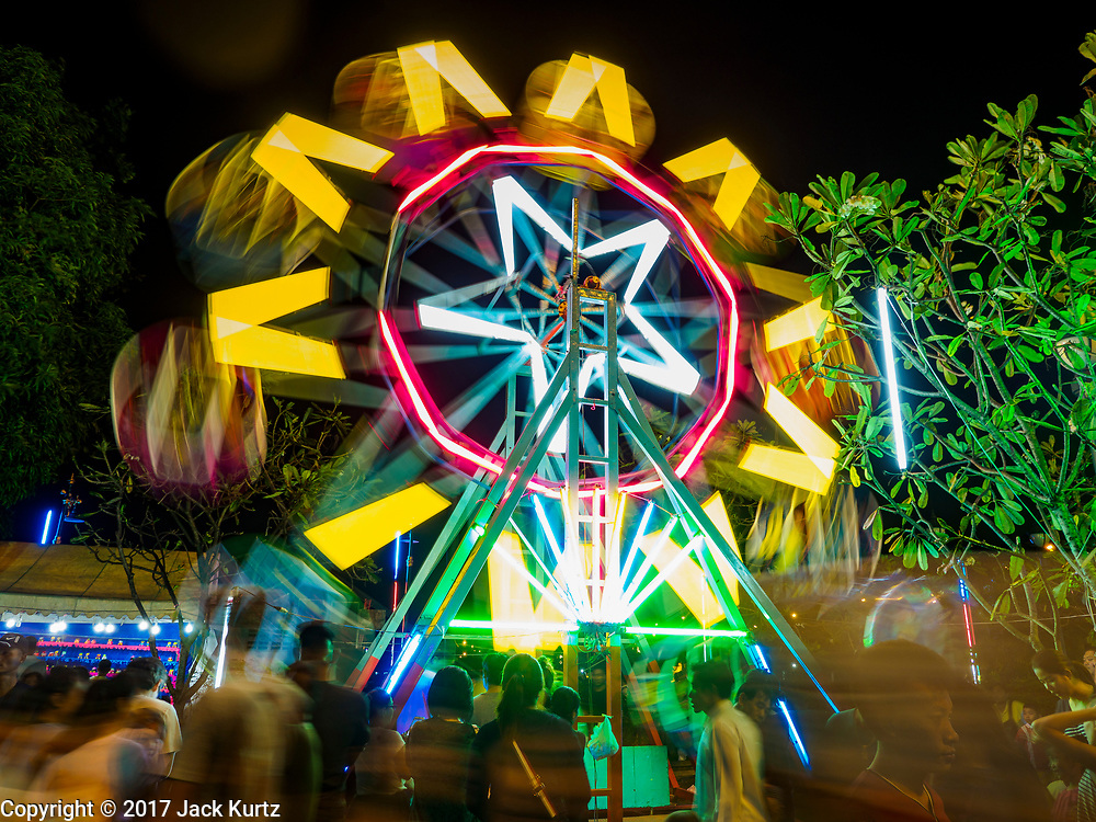 """03 NOVEMBER 2017 - BANGKOK, THAILAND: A Ferris Wheel entertains children during Loi Krathong at Wat Prayurawongsawat on the Thonburi side of the Chao Phraya River. Loi Krathong is translated as """"to float (Loi) a basket (Krathong)"""", and comes from the tradition of making krathong or buoyant, decorated baskets, which are then floated on a river to make merit. On the night of the full moon of the 12th lunar month (usually November), Thais launch their krathong on a river, canal or a pond, making a wish as they do so. Loi Krathong is also celebrated in other Theravada Buddhist countries like Myanmar, where it is called the Tazaungdaing Festival, and Cambodia, where it is called Bon Om Tuk.     PHOTO BY JACK KURTZ"""