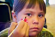 09 SEPTEMBER 2004 - WINDOW ROCK, AZ: A Navajo girl has her face painted in a booth during the 58th annual Navajo Nation Fair in Window Rock, AZ. The Navajo Nation Fair is the largest annual event in Window Rock, the capitol of the Navajo Nation, the largest Indian reservation in the US. The Navajo Nation Fair is one of the largest Native American events in the United States and features traditional Navajo events, like fry bread making contests, pow-wows and an all Indian rodeo.  PHOTO BY JACK KURTZ