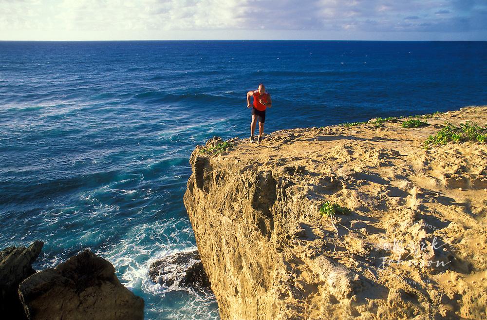 Man running along edge of seaside cliff, Kauai, Hawaii ****Model Release available
