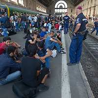 Line of riot police standing on the platform edge keeps illegal migrants away from railway tracks at the main railway station Keleti in Budapest, Hungary on September 03, 2015. ATTILA VOLGYI