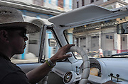 """A vintage cab driver behind the wheel of his 1953 Mercury with it's original motor. """"I am a trumpeteer,"""" he said. """"But I have a family and have to drive for a living."""""""