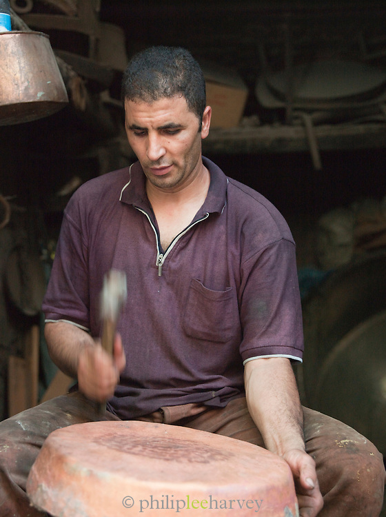 A metal worker shaping brass in his workshop in the medina of Fes, Morocco