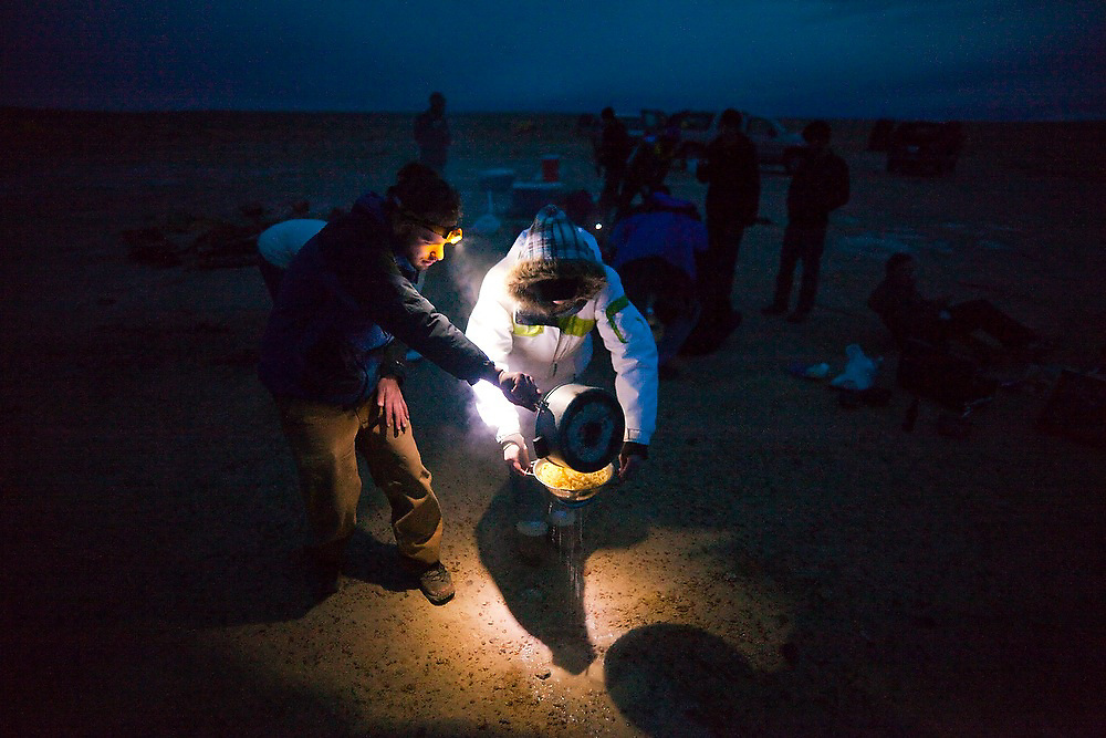 University of Colorado students on a geology field trip cook dinner by headlamp, straining spaghetti at their wilderness campsite on BLM land near Factory Butte, Utah.
