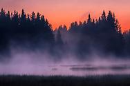 Smoke over a beautful mountain lake at summer dawn