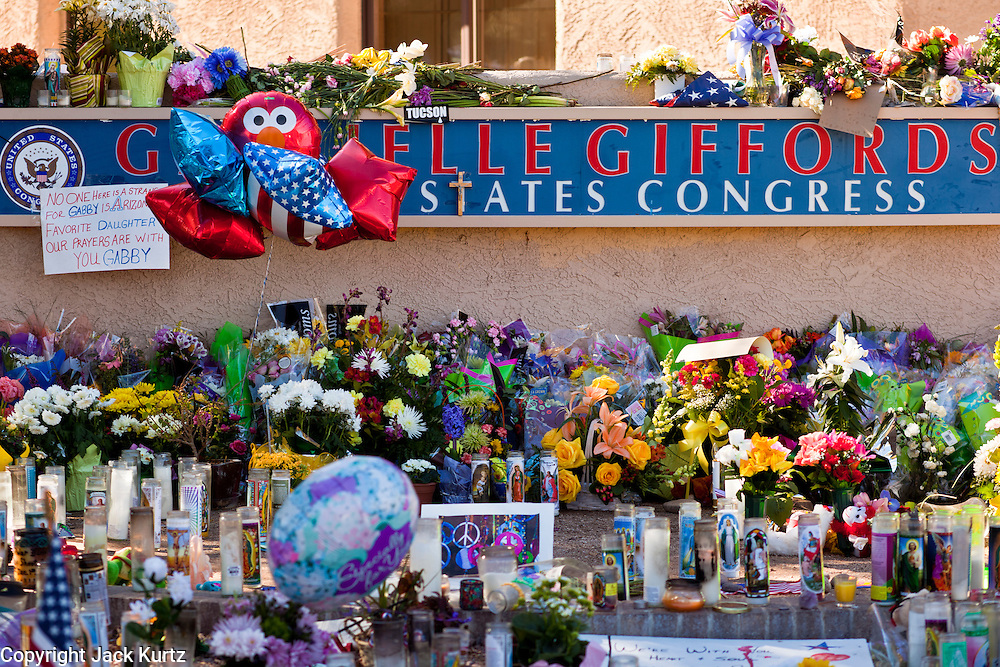 """15 JANUARY 2010 - TUCSON, AZ:    The memorial at Congresswoman Gabrielle Giffords office for victims of the mass shooting in Tucson, AZ, Saturday, January 15. Six people were killed and 14 injured in the shooting spree at a """"Congress on Your Corner"""" event hosted by Arizona Congresswoman Gabrielle Giffords at a Safeway grocery store in north Tucson on January 8. Congresswoman Giffords, the intended target of the attack, was shot in the head and seriously injured in the attack but is recovering. Doctors announced that they removed her breathing tube Saturday, one week after the attack. The alleged gunman, Jared Lee Loughner, was wrestled to the ground by bystanders when he stopped shooting to reload the Glock 19 semi-automatic pistol. Loughner is currently in federal custody at a medium security prison near Phoenix.  PHOTO BY JACK KURTZ"""