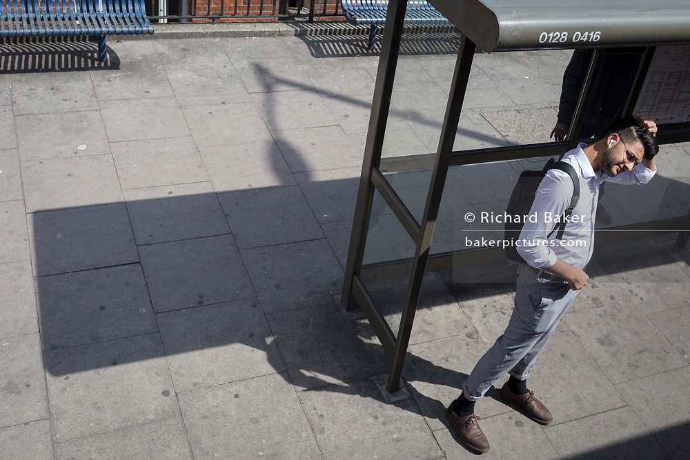 Seen from the window of a London bus, a man adjusts his hair on the Walworth Road in Southwark, south London, on 30th April 2019, in London, England