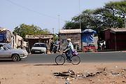 Een man rijdt op de fiets in Dakar.