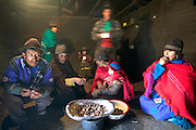 Ayme family members and relatives eat sitting on the dirt floor of the family's cooking house in Tingo, Ecuador. (Supporting image from the project Hungry Planet: What the World Eats.)