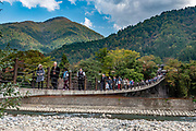 """Suspension bridge. Ogimachi is the largest village and main attraction of the Shirakawa-go region, in Ono District, Gifu Prefecture, Japan. Declared a UNESCO World Heritage Site in 1995, Ogimachi village hosts several dozen well preserved gassho-zukuri farmhouses, some more than 250 years old. Their thick roofs, made without nails, are designed withstand harsh, snowy winters and to protect a large attic space that was formerly used to cultivate silkworms. Many of the farmhouses are now restaurants, museums or minshuku lodging. Some farmhouses from surrounding villages have been relocated to the peaceful Gassho-zukuri Minka-en Outdoor Museum, across the river from the town center. Gassho-zukuri means """"constructed like hands in prayer"""", as the farmhouses' steep thatched roofs resemble the hands of Buddhist monks pressed together in prayer."""