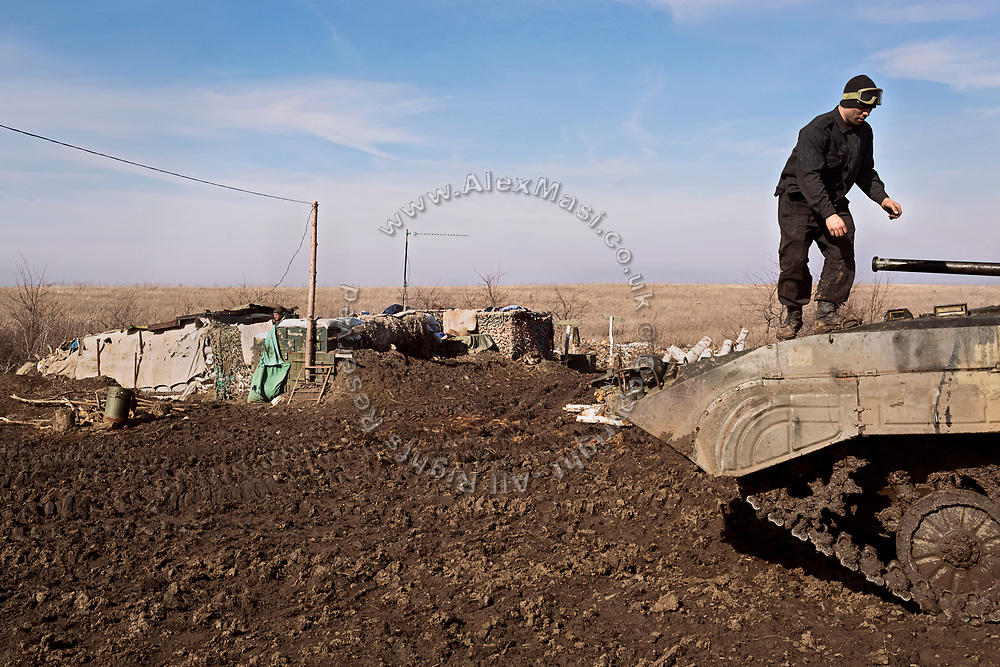 The driver of a BMP (infantry fighting vehicle) is standing on top of it while on the frontline of Myronivs'kyi, where soldiers are building small makeshift bases and digging trenches to defend their positions.
