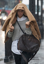 © licensed to London News Pictures. London, UK 11/06/2012. A woman uses a coat to protect her from heavy rain in Regent Street, today (11/06/12). Photo credit: Tolga Akmen/LNP