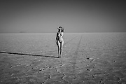 Monochrome photo of a woman posing at sunset on the Bonneville Salt Flats, Utahwith tire marks extending into the distance