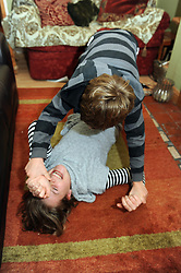 A sister and brother fight on the living room floor MODEL RELEASED
