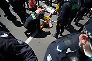 Police speak with protesters who have attached themselves to the road during an Extinction Rebellion protest in Melbourne.  A small group of climate protesters marched from Flagstaff Gardens to The Queen Victoria Market and ending with two individuals gluing themselves together, and then glued themselves to Victoria Avenue outside of the Market. This comes as 5 new COVID-19 cases were uncovered in Melbourne's revamped Hotel Quarantine, breaking almost 40 days of virus free days. (Photo by Dave Hewison/Speed Media)