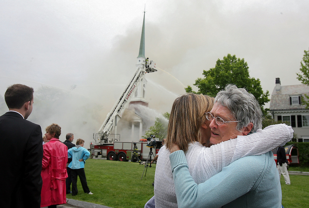 (051709 Cambridge, MA)  From left, Jane Johnson, of Belmont, hugs Jo Ellen Hillyer, as they watch the Jesus Christ Church of Latter-Day Saints on Longfellow Park in Cambridge burn in a fire that started during Sunday mass.
