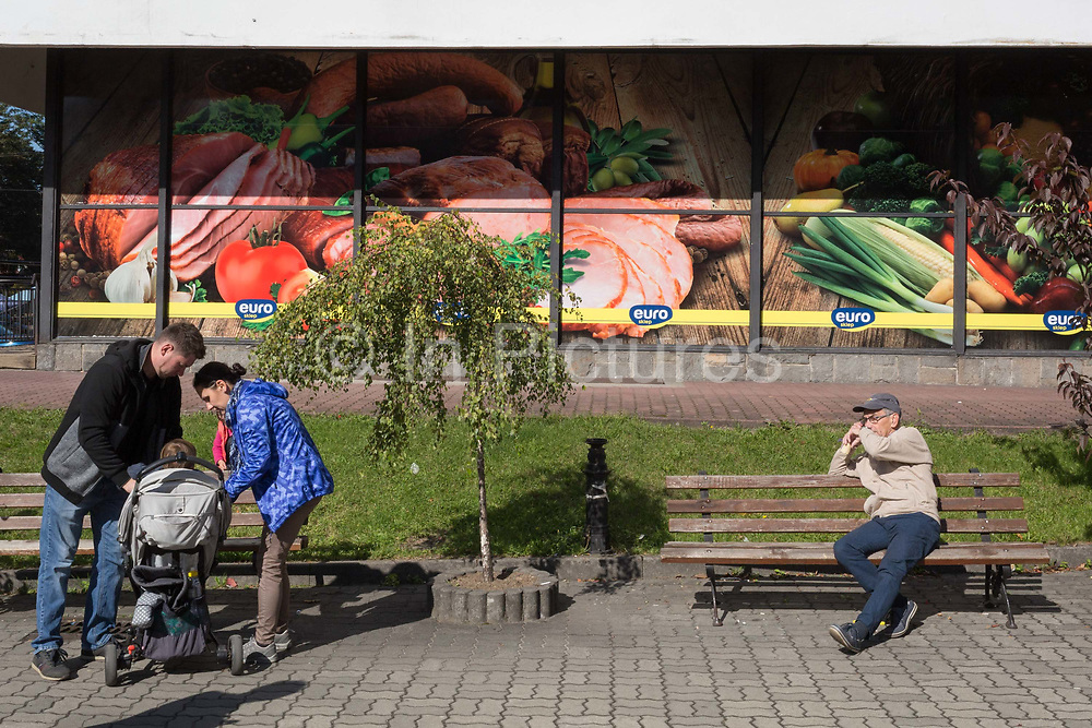 Polish parents attend to their child in front of billboards for a local Euro supermarket, on 21st September 2019, in Szczawnica, Malopolska, Poland.