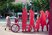 Woman walks past a piece of public art depicting a cut out in pink of Shanghainese people on Nanjing Road.