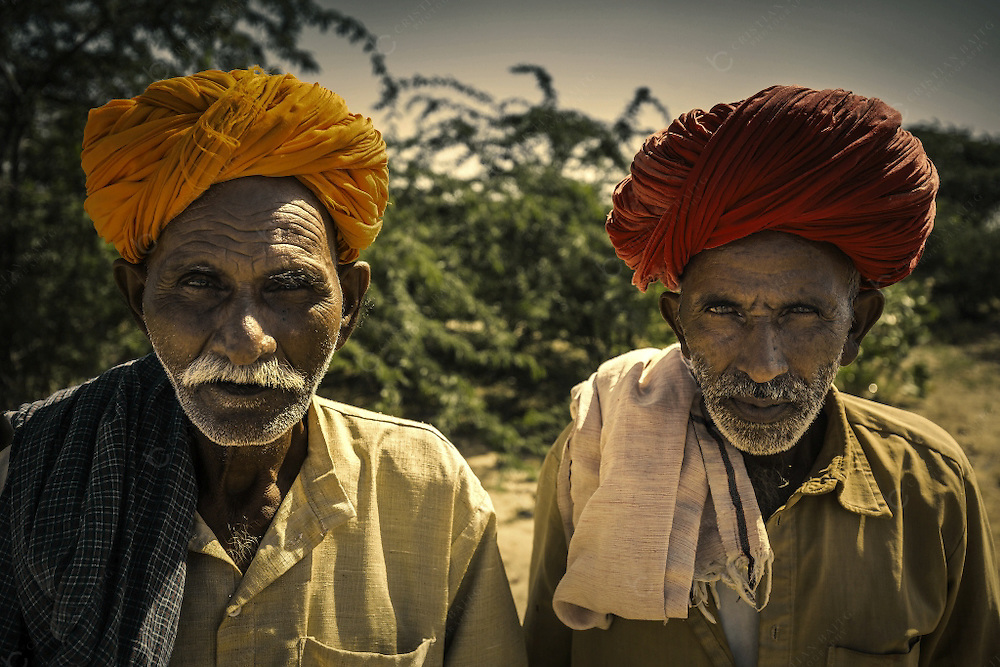 Two senior men on the side of the road between Jaisalmer and Pokhran in the Thar desert. The same way as women wear colorful saris many men in Rajasthan wear this colorful garments