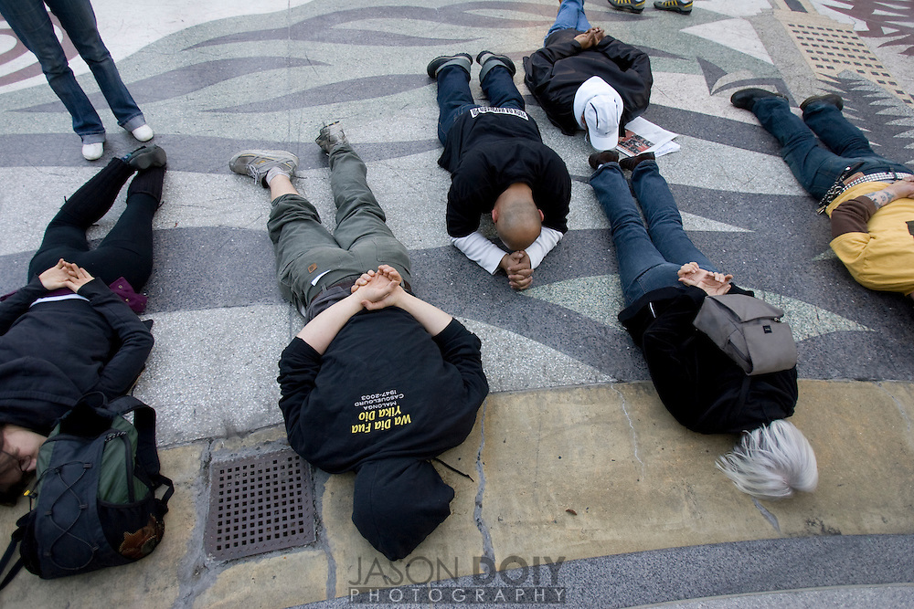 Dozens of protestors lie down as if under arrest in front of Oakland's City Hall as the names of victims of police shootings are read to the crowd. The protest comes hours after attorney Christopher Miller held a press conference in Sacramento on behalf of the Bart Police officer Johannes Mehserle,who was charged with murder for his shooting of Oscar Grant...Photo by Jason Doiy.1-14-09.047-2009