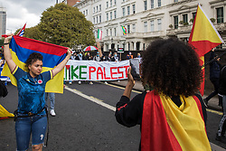 London, UK. 15th May, 2021. An activist draped with a Tigray flag addresses hundreds of people taking part in a Free Palestine SOS Colombia solidarity march from the Colombian embassy to the Israeli Embassy as they pass the Ethiopian embassy. Speakers highlighted human rights abuses such as forced displacement being directed against Palestinians in Israel and the Occupied Territories, the killing, repression, detention and torture of peaceful demonstrators and human rights defenders in Colombia and the use of mass killings, rape, ethnic cleansing and starvation as a weapon of war in Tigray.