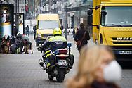 Corona Lockdown, March 18th. 2021. Policeman on motorcycle on patrol on shopping street Schildergasse, Cologne, Germany.<br /> <br /> Corona Lockdown, 18. Maerz 2021. Polizist auf Motorrad kontrolliert in der Einkaufsstrasse Schildergasse, Koeln, Deutschland.