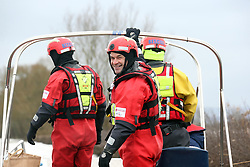 © Licensed to London News Pictures. 03/02/2014. Somerset, UK. Avon and Somerset police boatmen in yellow and Devon and Somerset fire and rescue boatmen in red. The day before Prince Charles visits the Somerset flooding, boats ferrying locals in and out of Muchelney. The Prince will chat to residents in the flood-hit community of Muchelney on Tuesday and travel to meet a nearby farming family at their home. Photo credit : Jason Bryant/LNP