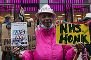 A woman holds signs in support of the National Health Service at a rally organised by Doctors in Unite outside the Department of Health and Social Care on 5th July 2021 in London, United Kingdom. The rally was organised to mark the 73rd birthday of the National Health Service and in protest against the sale of one of the UK's biggest GP practice operators to the US health insurance group Centene Corporation.