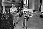 Nederland, Nijmegen, 15-9-1988Vanwege het 65-jarig bestaan van de Radboud universiteit, destijds katholieke universiteit nijmegen, presenteerd rector magnificus Bas van Iersel in het gemeentehuis de stadsbus met daarop de naam van de universiteit. Burgemeester Dales kijkt intussen op haar horloge.Foto: Flip Franssen/Hollandse Hoogte