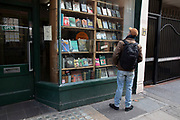 People pass rare and second hand book shop window on Charing Cross Road on 18th February 2020 in London, England, United Kingdom. Charing Cross Road is renowned for its specialist and second-hand bookshops, and is home to many book shops, and more general second-hand and antiquarian shops.
