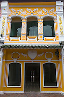 """One of the features of Phuket shophouses  or """"row houses"""" is the front verandahs form a sheltered walkway and intricate stucco designs often grace their facades. Many walkways and interiors are covered with ceramic tiles with elaborate European motifs.  Phuket has a long association with European trading nations:  Portugal, Great Britain and France with an established population of ethnic Chinese. Phuket City has always been a meeting place of Thai and Malays and the overall result was a fascinating mixture of architecture - therefore the look and feel of old Phuket is unique in Thailand."""