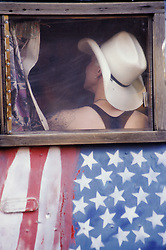 North America, United States, New Mexico, Santa Fe, woman in cowboy house in window of bus painted with American flag
