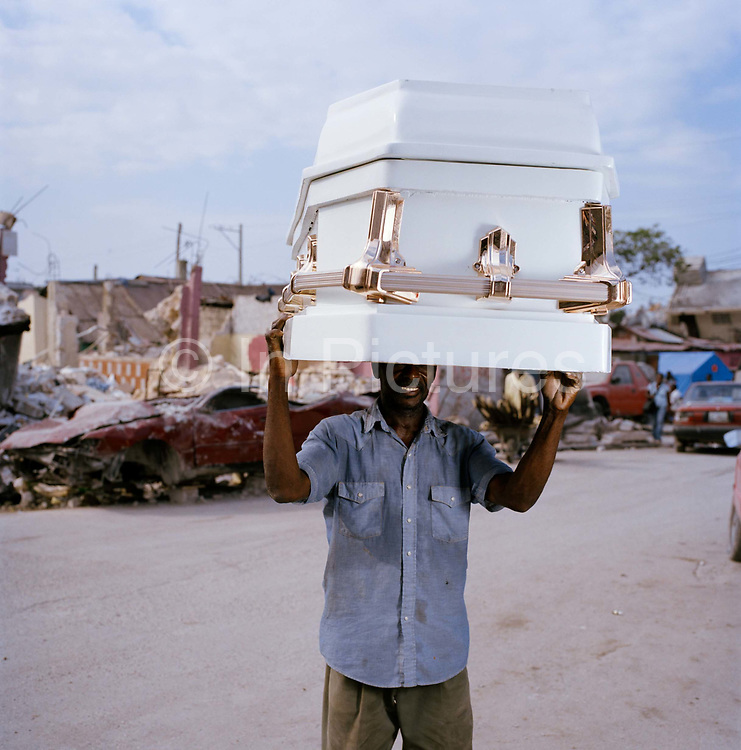 A Haitian carries a heavy coffin the mile or so to the central hospital morgue. On Tuesday 12th of January at 16.53pm local time the biggest Earthquake to hit Haiti for 200 years struck with devastating force. 230,000 people were killed, 300,000 injured and 1.2 million left needing emergency shelter. Survivors have lost family, homes, livelihoods and essential services. Hospitals, schools and government buildings were also destroyed'. These pictures are of the survivors three weeks later.
