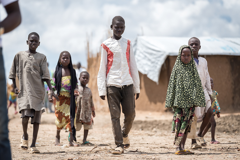 30 May 2019, Mokolo, Cameroon: Children walk through the Minawao camp for Nigerian refugees.  The Minawao camp for Nigerian refugees, located in the Far North region of Cameroon, hosts some 58,000 refugees from North East Nigeria. The refugees are supported by the Lutheran World Federation, together with a range of partners.