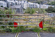 Railway tracks disappear into undergrowth near housing, on 6th October 2021, in Blaenau Ffestiniog, Gwynedd, Wales. The derelict slate mines around Blaenau Ffestiniog in north Wales were awarded UNESCO World Heritage status in 2021. The industry's heyday was the 1890s when the Welsh slate industry employed approximately 17,000 workers, producing almost 500,000 tonnes of slate a year, around a third of all roofing slate used in the world in the late 19th century. Only 10% of slate was ever of good enough quality and the surrounding mountains now have slate waste and the ruined remains of machinery, workshops and shelters have changed the landscape for square miles.