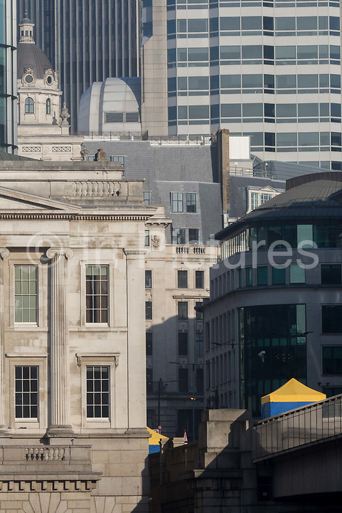 The morning after the terrorist attack at Fishmongers Hall on London Bridge, in which Usman Khan a convicted, freed terrorist killed 2 during a knife a attack, then subsequently tackled by passers-by and shot by armed police - the forensic tent where the killer was brought down is positioned next to Fishmongers Hall, on 30th November 2019, in London, England.