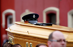 © Licensed to London News Pictures. 22/03/2016. Belfast, Northern Ireland, UK. The hat and gloves on the coffin of murdered prison officer Adrian Ismay as it leaves Woodvale Methodist church. Mr Ismay died following a booby-trap bomb that exploded under his van in East Belfast on March 4th. Photo credit: Peter Morrison/LNP
