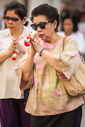 "25 FEBRUARY 2013 - BANGKOK, THAILAND: Thai women bow their heads as they enter Wat Benchamabophit Dusitvanaram (popularly known as either Wat Bencha or the Marble Temple) on Makha Bucha Day. Makha Bucha is a Buddhist holiday celebrated in Myanmar (Burma), Thailand, Cambodia and Laos on the full moon day of the third lunar month (February 25 in 2013). The third lunar month is known in Thai is Makha. Bucha is a Thai word meaning ""to venerate"" or ""to honor"". Makha Bucha Day is for the veneration of Buddha and his teachings on the full moon day of the third lunar month. Makha Bucha Day marks the day that 1,250 Arahata spontaneously came to see the Buddha. The Buddha in turn laid down the principles his teachings. In Thailand, this teaching has been dubbed the 'Heart of Buddhism'.      PHOTO BY JACK KURTZ"