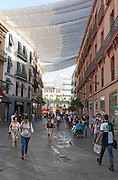 Fabric spread over buildings to provide shade in busy shopping street in central Seville, Spain