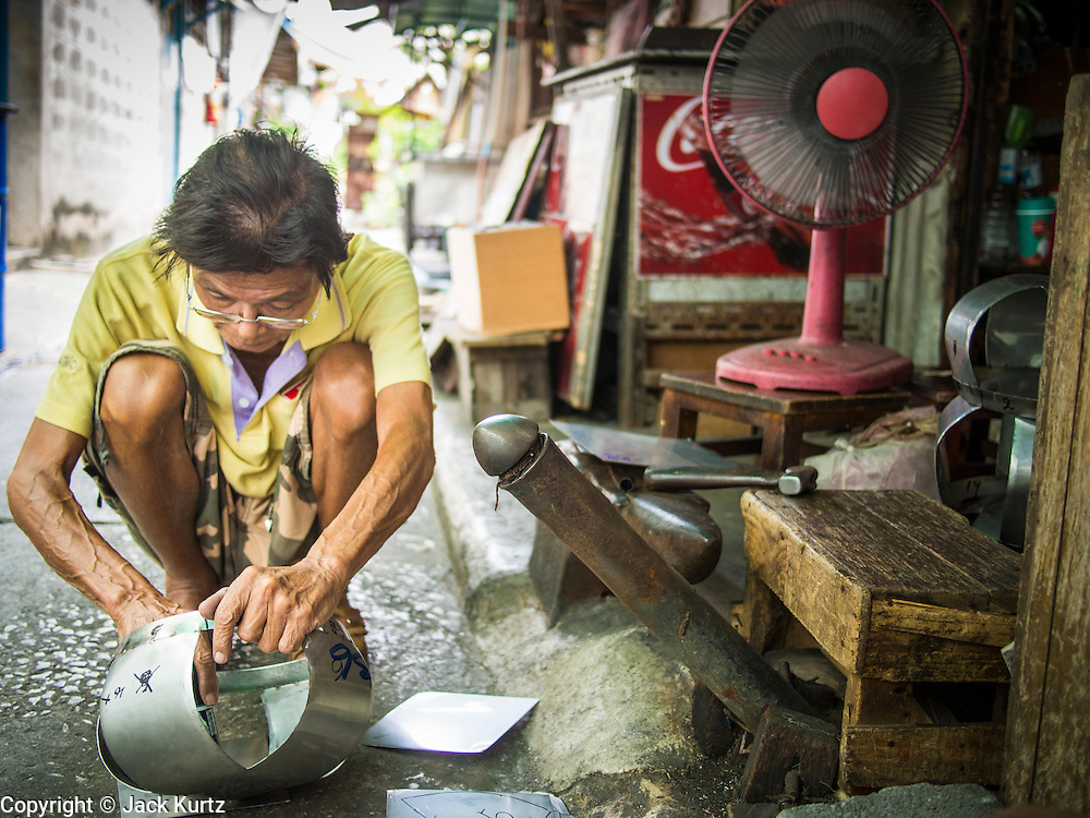 """19 AUGUST 2013 - BANGKOK, THAILAND:     A man makes monks' bowls, called """"bat"""" (pronounced with a long """"a"""" as in baat) on Soi Baan Bat in Bangkok. The bowls are made from eight separate pieces of metal said to represent the Buddha's Eightfold Path. The Monk's Bowl Village on Soi Ban Baat in Bangkok is the only surviving one of what were originally three artisan's communities established by Thai King Rama I for the purpose of handcrafting """"baat"""" the ceremonial bowls used by monks as they collect their morning alms. Most monks now use cheaper factory made bowls and the old tradition is dying out. Only six or seven families on Soi Ban Baat still make the bowls by hand. Most of the bowls are now sold to tourists who find their way to hidden alleys in old Bangkok. The small family workshops are only a part of the """"Monk's Bowl Village."""" It is also a thriving residential community of narrow alleyways and sidewalks.  PHOTO BY JACK KURTZ"""